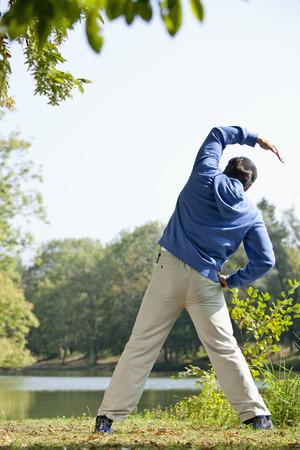 sweatshirt: Man stretching beside lake