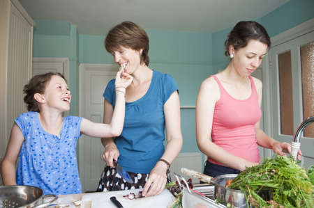 woman in bath: Mother cooking with her two daughters LANG_EVOIMAGES