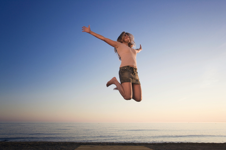 prevailing: Woman on beach jumping for joy