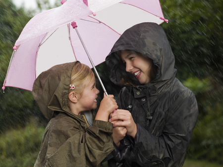 drizzling rain: Girls huddled under an umbrella LANG_EVOIMAGES