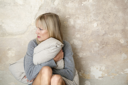 struggled: woman sitting on floor with pillow
