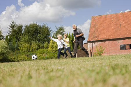 level playing field: grandfather and kids playing football