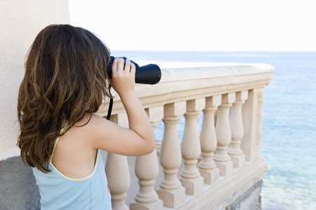 Girl with binoculars looking out to sea
