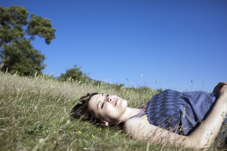 lays down: Woman relaxing on hill