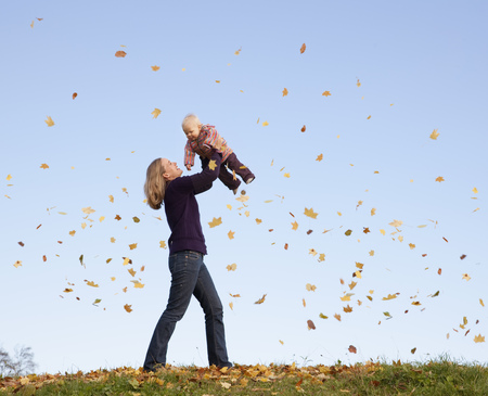 tosses: mother lifting baby in flying leaves