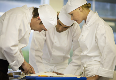 Three chefs filleting a fish LANG_EVOIMAGES