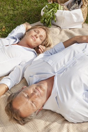doze: Middle aged couple on a picnic blanket LANG_EVOIMAGES