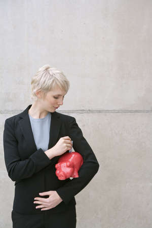 held down: woman in suit with piggy bank LANG_EVOIMAGES