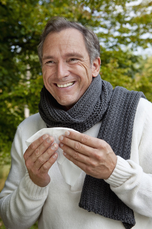 Middle aged man with scarf and tissue