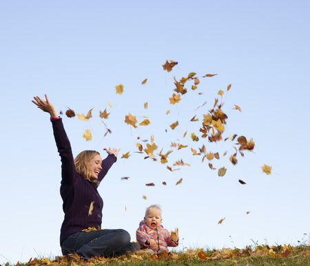 regard: mother and baby throwing autumn leaves LANG_EVOIMAGES
