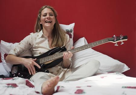 kvinna spelar gitarr på sängen
