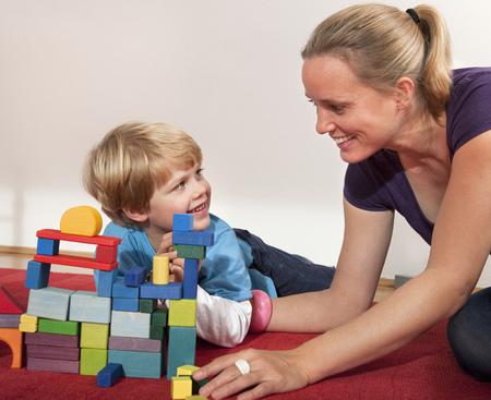 agachado: madre e hijo juegan con bloques de construcción