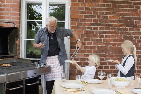 waits: grandfather barbecuing for children LANG_EVOIMAGES