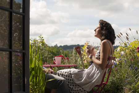 refreshed: woman on balcony drinking tea LANG_EVOIMAGES
