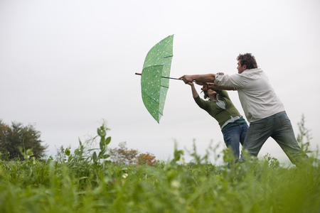 couple with umbrella in windy field LANG_EVOIMAGES