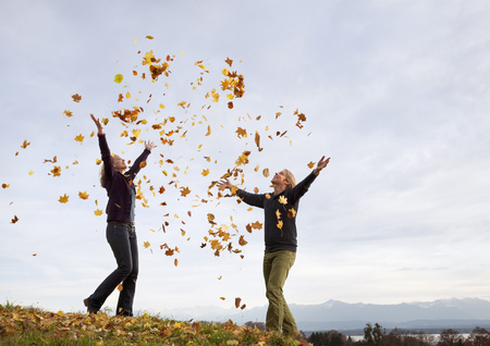 tosses: woman and man throwing autumn leaves