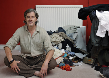 decide deciding: man with pile of clothes