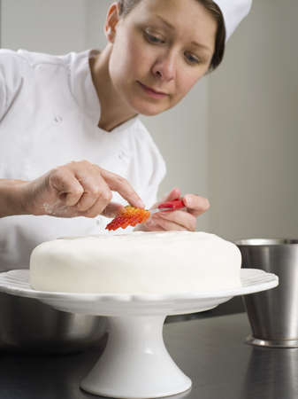 new age: A female chef cake decorating LANG_EVOIMAGES