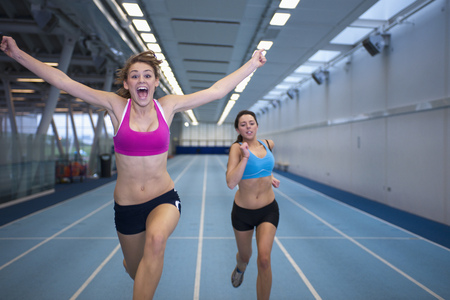 enthusiastically: 2 female athletes racing LANG_EVOIMAGES