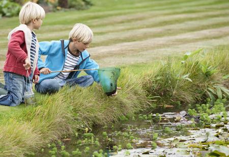 agachado: Brothers with fishing net near pond