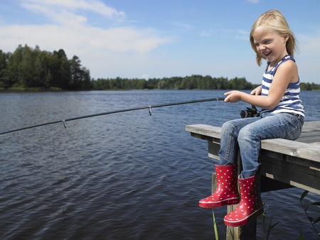 midsummer pole: Girl fishing from a dock