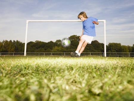 Boy kicking football in front of goal LANG_EVOIMAGES