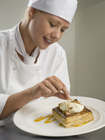 A female chef finishing a desert LANG_EVOIMAGES