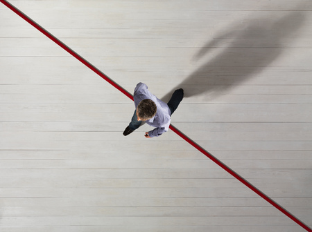 stepping: Business man stepping over a red line