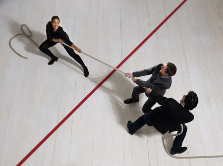 Business men pulling woman with rope