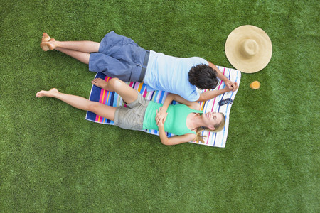 lays down: Couple resting in a garden