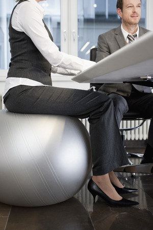 low section: Businesswoman sitting on gym ball