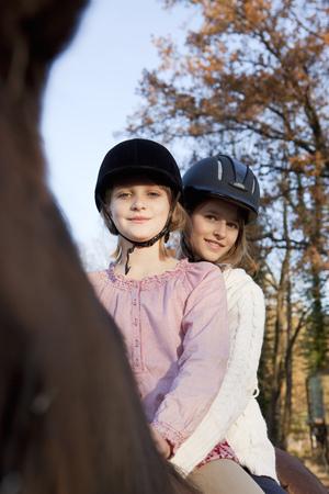 Two girls on a horseback LANG_EVOIMAGES