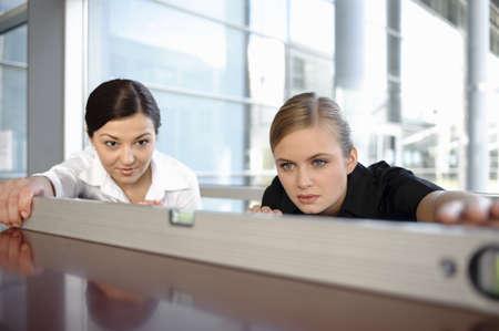 toils: Two businesswomen using spirit level