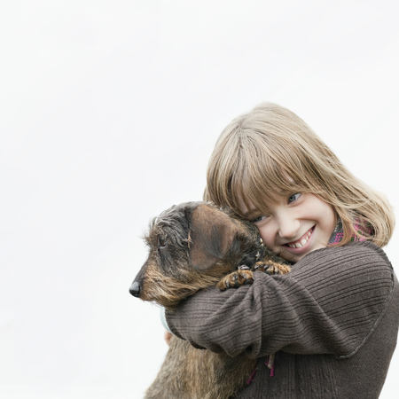 Portrait of girl embracing dog in arms
