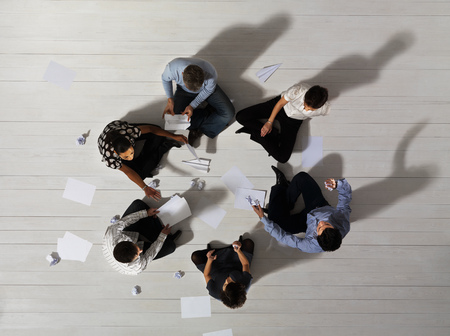 accomplishes: Business men and women sitting in circle