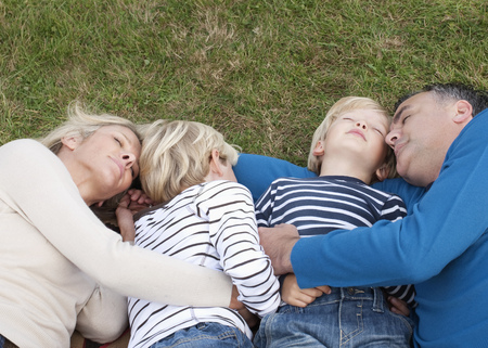 brotherly love: Family lying down together on grass