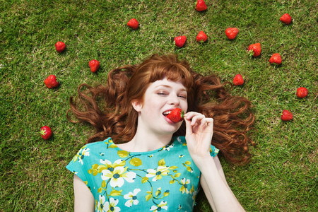 sweet grasses: girl in grass surrounded by strawberries