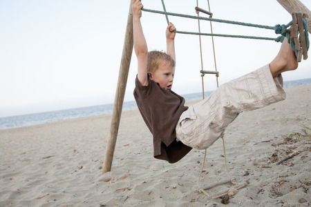 limber: Boy on a swing at the beach