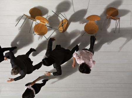 met: Business people knocking over chairs LANG_EVOIMAGES
