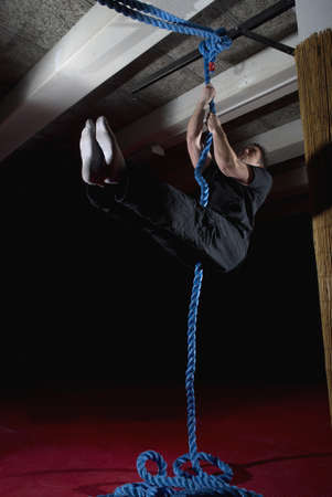 climbed: man doing rope exercises