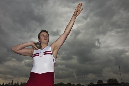 man putting shot with arm raised