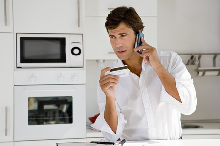 commanded: Man on phone with credit card
