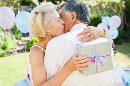 mature woman kisses mature man.