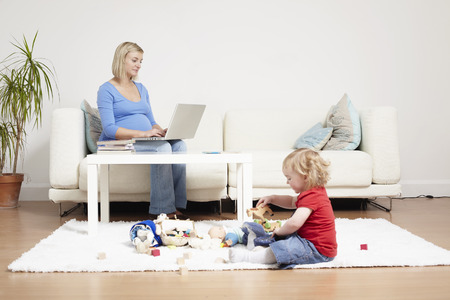 Woman on a laptop at home with toddler