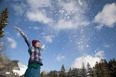 low spirited: Girl throwing snow into the air