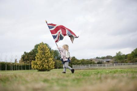 Little girl holding up flag LANG_EVOIMAGES