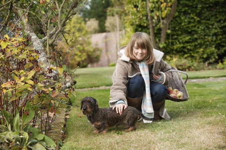 Girl with basket and dog in garden LANG_EVOIMAGES