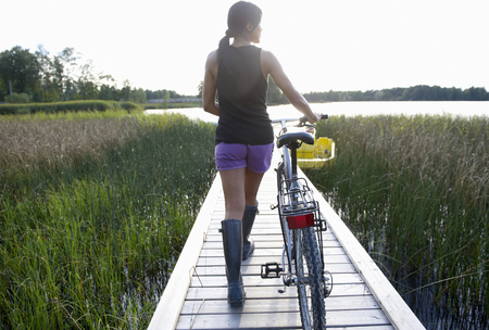 Woman with her bike, on a dock