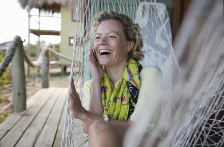 joyous: woman in a hammock, talking on the phone