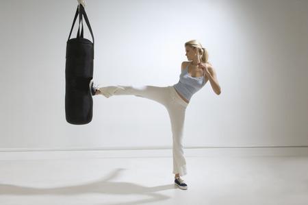 Female kicking punchbag LANG_EVOIMAGES